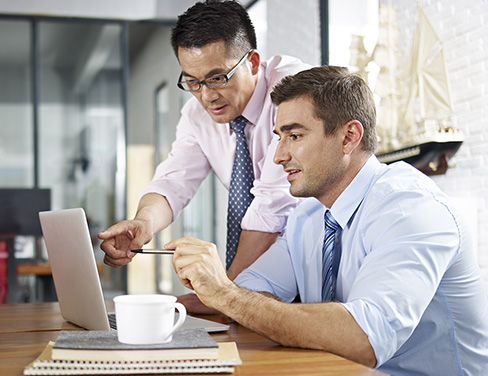 Two men working on a laptop