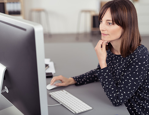 A woman working on a desktop computer